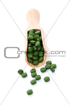 Green pills on wooden spoon isolated.