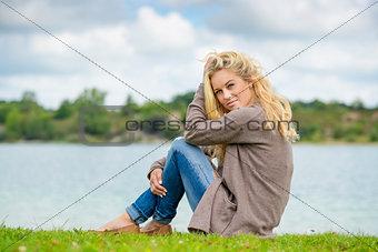 Blond woman sitting at lake