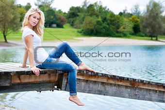 Blond woman sitting on a jetty