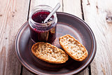 black currant jam in glass jar and crackers