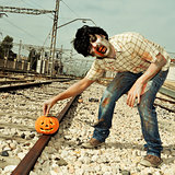 zombie putting a carved pumpkin on the railroad tracks