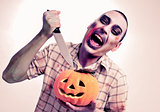 zombie about to stick a knife into a carved pumpkin