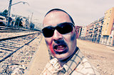 scary zombie with sunglasses at abandoned railroad tracks, with