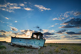 Abandoned fishing boat on beach landscape at sunset