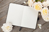 Blank notepad and white rose flowers