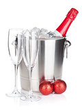 Champagne bottle in ice bucket, two empty glasses and christmas
