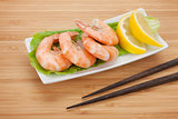 Cooked shrimps with lemon and chopsticks
