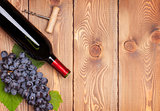 Red wine bottle and bunch of red grapes