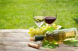 White and red wine glasses and bottle with bunch of grapes