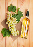 White wine bottle and bunch of white grapes