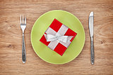 Gift box on plate and silverware