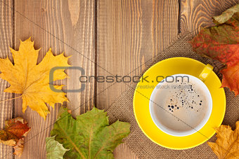 Autumn leaves and coffee cup over wood background