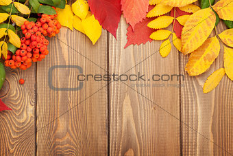 Autumn leaves over wood background