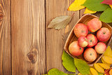 Autumn leaves and apples over wood background