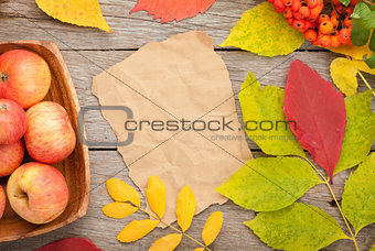 Autumn leaves, rowan berries and apples over wood background