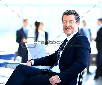 Casual businessman working in office, sitting at desk.