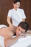 Man receiving shoulder massage at spa center