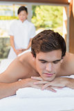Man lying on massage table at spa center