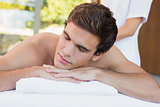 Young man lying on massage table at spa center