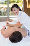 Man receiving back massage at spa center