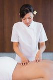 Female masseur massaging mans back at spa center