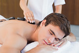 Young man receiving stone massage at spa center