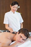 Man receiving stone massage at spa center