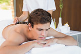 Man receiving stone massage at spa center