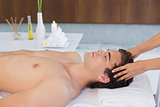 Young man receiving head massage at spa center