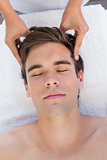 Man receiving head massage at spa center