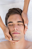 Man receiving facial massage at spa center