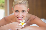 Woman holding flower on massage table at spa center