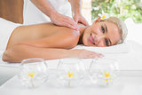 Woman receiving shoulder massage at spa center