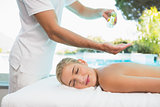 Woman receiving back massage at spa center