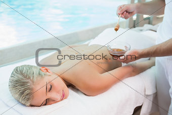 Attractive woman receiving spa treatment with honey
