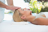 Attractive woman receiving head massage at spa center
