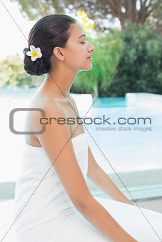 Beautiful woman sitting with eyes closed at spa center