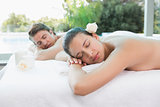 Couple lying on massage table at spa center