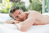 Handsome man lying on massage table at spa center