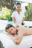 Handsome man receiving stone massage at spa center
