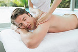 Handsome man receiving shoulder massage at spa center