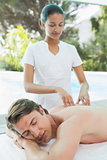 Handsome man receiving back massage at spa center