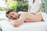 Handsome man receiving back massage at spa center