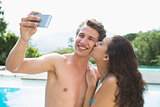 Couple taking picture of themselves by swimming pool on a sunny day