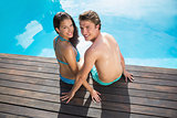 Romantic young couple by swimming pool on a sunny day