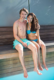 Romantic young couple by swimming pool