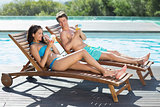 Couple sitting on sun loungers by swimming pool