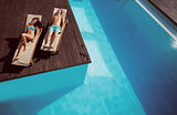 Couple resting on sun loungers by swimming pool