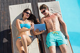 Couple using digital tablet on sun loungers by swimming pool