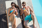 Couple with drinks on sun loungers by swimming pool